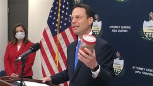 Pennsylvania Attorney General Josh Shapiro, right, holds a jar of discolored tap water during a news conference. He said the sample was from the home of a state resident whose well had been tainted by nearby natural gas drilling.