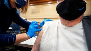 Amber Pedro, a volunteer from Family Practice Laporte, administers the vaccine into the arm of Robert Keen, 84 of Forksville, in the cafeteria of the Sullivan County Elementary School.