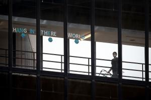 "A sign that reads ""HANG IN THERE WORLD"" is seen in the windows of the enclosed walkway at Thomas Jefferson University Hospital in Philadelphia. State officials are asking hospitals to work together as some face a staffing crisis."