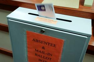A ballot is deposited into a box at the county clerk's office in Erie. A newly approved resolution is meant to bar groups of people openly carrying firearms from gathering near polling places and drop boxes.
