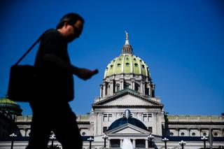 Man walks in front of Pennsylvania state capitol