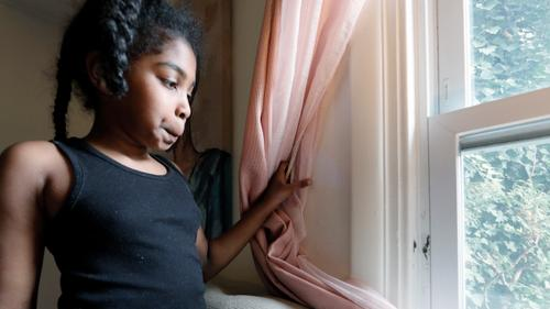 Jasmine Pennington's daughter Nylah Green, 9, pulls a bedroom curtain back revealing mold growing around the window in their Philadelphia rental unit.