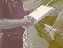 A police officer writes a ticket for a motorist