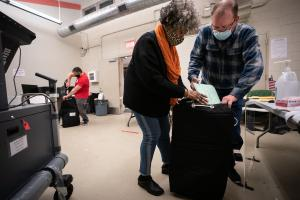 Three election workers put provisional ballots in the hopper at the 5th and 9th division of the 26th Ward after the polls closed at the polling place at Barry Recreation Center, in South Philadelphia, on Election Day.
