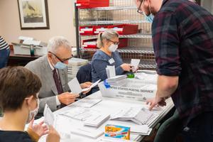 Volunteers open and sort mail-in ballots in Erie while poll watchers observe.