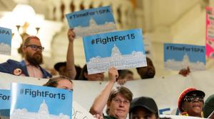 People hold up signs during a press conference and rally in 2019 calling for a $15 minimum wage.