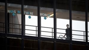 """A sign that reads """"HANG IN THERE WORLD"""" is seen in the windows of the enclosed walkway at Thomas Jefferson University Hospital in Philadelphia. State officials are asking hospitals to work together as some face a staffing crisis."""