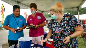 Luis Angel Guzman, a 19-year-old carnival ride worker from Mexico, talks with Wayne Memorial Community Health Center nurses at the Wayne County Fair before he got the Johnson & Johnson vaccine.
