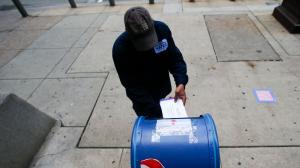A person drops an absentee ballot into a mailbox.