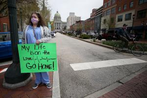 Nurse Erica Zimmerman, of southwestern Pennsylvania, urges protesters who gathered outside the Capitol Complex to go home during a rally in Harrisburg, PA on April 20, 2020. The protesters are calling for Gov. Wolf to reopen up the state's economy during the coronavirus outbreak.