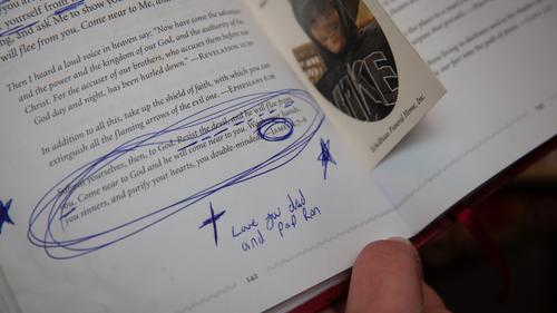 """Amanda Pschirer holds a copy of the religious book """"Jesus Calling"""" that belonged to her late brother, James Pschirer, in McCandless, Pennsylvania on Thursday, Feb. 25, 2021. Among underlined sentences and circled paragraphs, James wrote """"Love you dad and pap Ron,"""" referring to his biological father, James Pschirer, and his stepfather, Ron Zack, both of whom preceded him in death."""