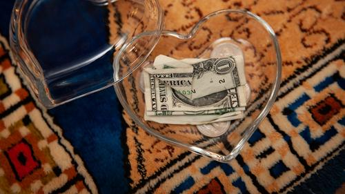 A couple of dollars and some change once belonging to James Pschirer sit in a heart-shaped glass container as photographed Thursday, Feb. 25, 2021.