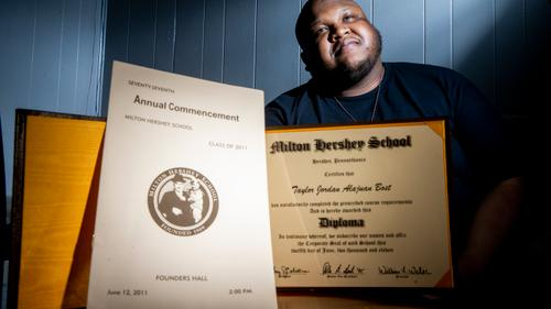 Taylor Bost, 28, with his diploma and commencement program