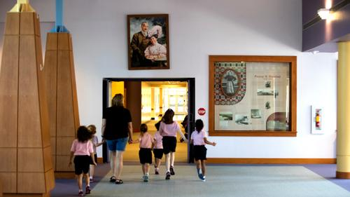 A group passes under a portrait of Milton and Catherine Hershey in Fanny Hershey Memorial Hall at the Milton Hershey School