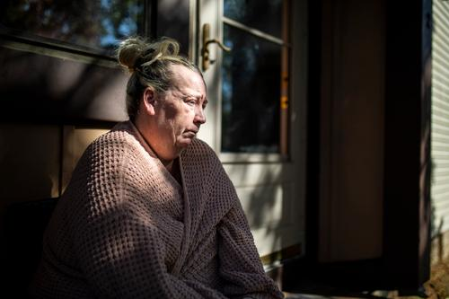 Laura Gallagher, of Langhorne, Pa., sits at the front of her home on Wednesday, Oct. 14, 2020.